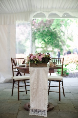 small wooden sweetheart table with rustic centerpiece and lace table runner