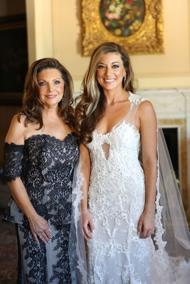 bride in monique lhuillier wedding dress with cape veil and mother in black lace dress long hair