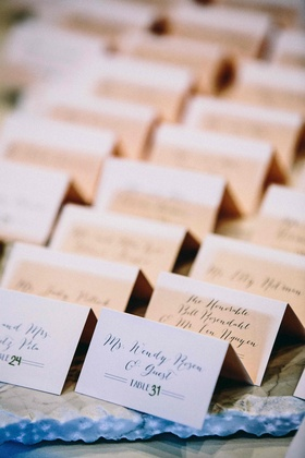 small white folded escort cards featuring calligraphy