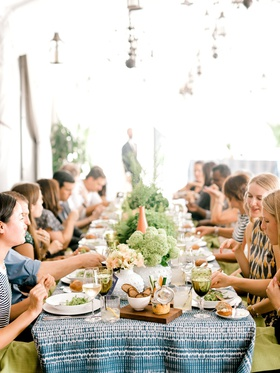 guests at boho chic bridal shower rooftop blue white batik linens greenery centerpieces summer event