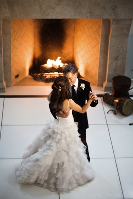 bride and groom dance in front of fireplace