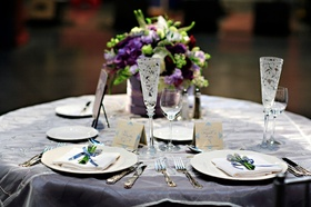 Wedding reception sweetheart table with a centerpiece of purple and white flowers
