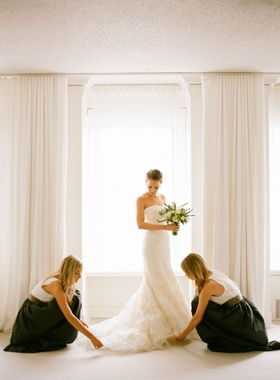 bridesmaids in black skirts and white tops lay out bride's vera wang gown train