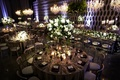 dark lighting at wedding reception, white roses and greenery in tall centerpiece