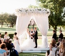 Bride in wedding dress black tux on groom chandelier outdoor wedding ceremony all white decor flower