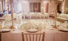 Reception ballroom with rectangular table with linens, ivory flowers, gold candelabra wedding ideas