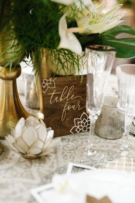 dark wood walnut table number with moroccan flower design and gold lettering modern calligraphy