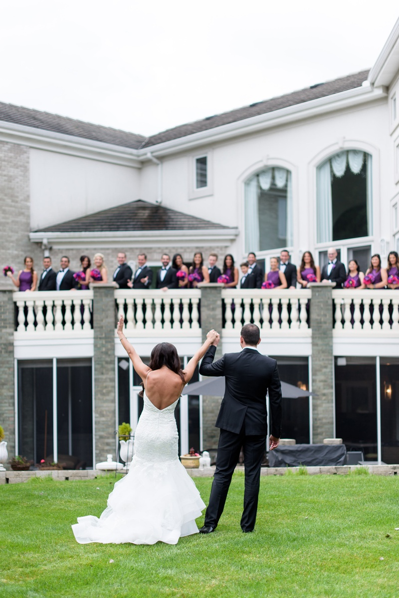 bride in monique lhuillier mermaid wedding dress, groom in gibeon tolbert wave to bridal party on ba