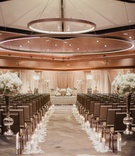 Ballroom wedding ceremony persian wedding with round lights overhead square chairs white flowers