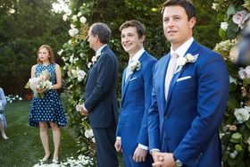 groom in blue suit next to officiant and maid of honor in blue dress