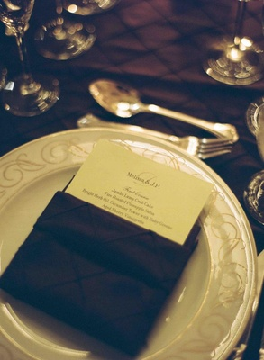 Menu card tucked into dark textured napkin