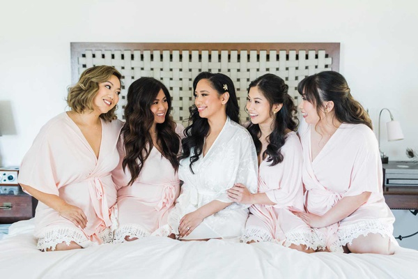 bride in white robe with bridesmaids on bed in pink robes with lace hem