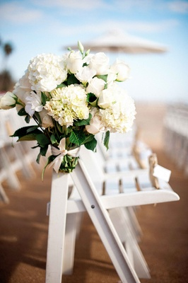 Bouquet of white hydrangeas, roses on folding chair at beach wedding ceremony