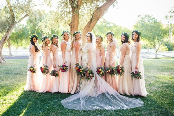 Bride in a Claire Pettibone dress with gold and silver embroidery, bridesmaids in pale pink dresses