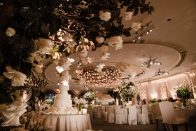 Ballroom wedding with chair covers tall wedding cake fresh greenery ivory flowers suspended