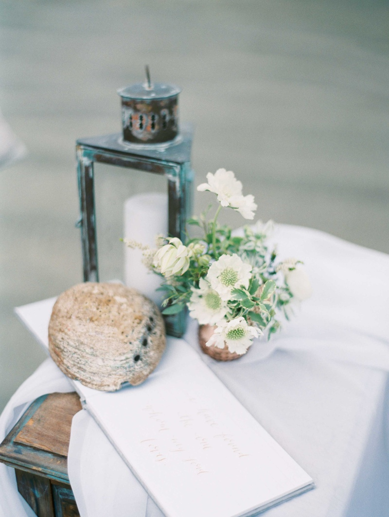 white guest book with rose gold calligraphy with driftwood small floral arrangement antique lantern