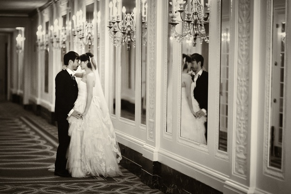 Black and white photo of couple in mirror and hallway