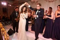 Bride in Inbal Dror wedding dress dancing with band saxophone player with tambourine at wedding
