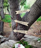 Outdoor wedding with direction signs made of arrow cutouts placed on a bow