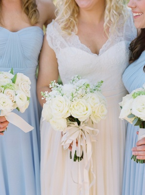 Bride in white lace dress bridesmaids in light blue gowns white rose bouquet ivory ribbon
