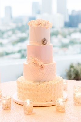 White wedding cake with blush silver and gold details flowers quilting candles roses simple topper