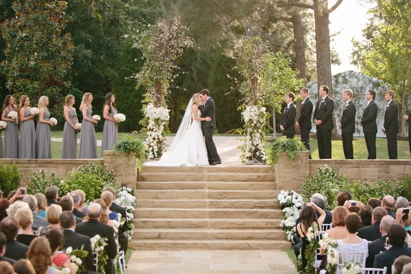 Young couple on top of steps kissing at wedding