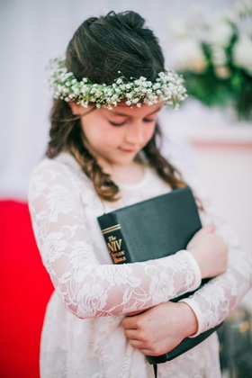 flower girl in lace long sleeve dress with baby's breath flower crown hugging bible holiday wedding