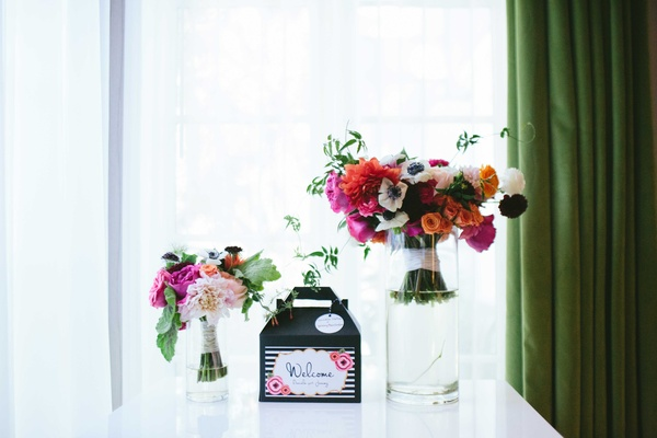black-and-white welcome boxes  with bright fuchsia bouquets