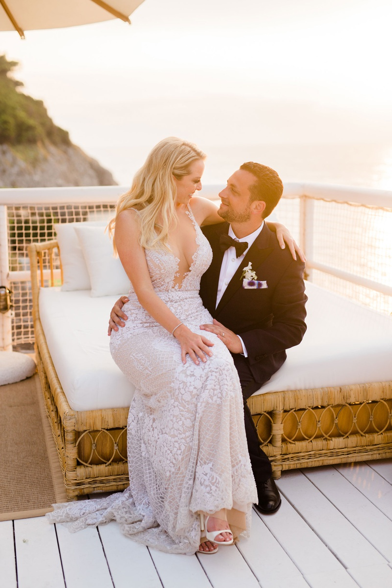 bride in galia lahav dress with plunging neckline sitting on lap of groom