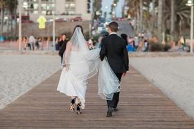 bride carries wedding dress train, groom carries cathedral veil, bride and groom walking on pier