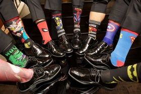 Groomsmen in dress shoes and slacks with superhero theme socks hulk spiderman superman batman more
