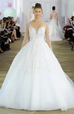 Full beaded ball gown with beaded illusion neckline and sleeve and corset bodice with natural waist.