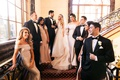 bride and groom on stairs with bridesmaids in off shoulder gowns and groomsmen in tuxedos white