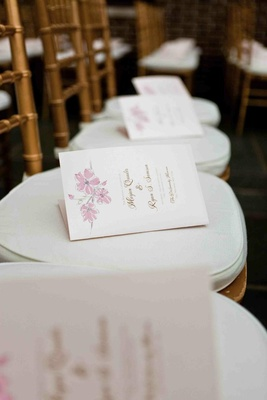 Wedding ceremony programs on chairs with floral motif
