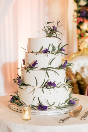 wedding cake four layer buttercream frosting fresh greenery and purple lavender flowers cake server