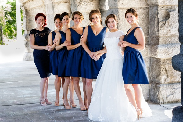 Bride in a line gown with bridesmaids in short v neck cocktail dresses hair updo
