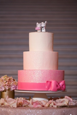 Wedding cake with two pink layers, white layer, glittery sheen, hot pink bow, custom bunny toppers