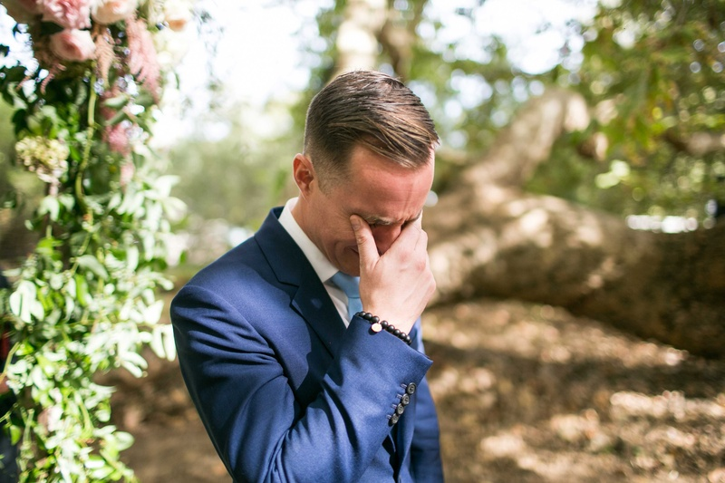Groom in navy blue suit holding back tears crying at outdoor wedding ceremony