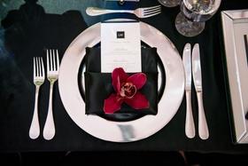 Wedding reception place setting silver charger plate black napkin burgundy orchid menu monogram