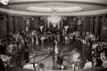 Black and white photo of bride and groom first dance in center of dance floor guests watching