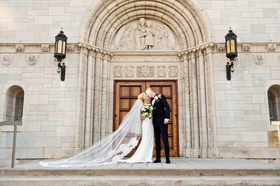 wedding portrait bride and groom kiss in front of church doors catholic church wedding