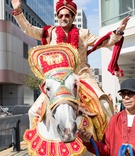 groom in traditional indian wedding attire before ceremony processional on decorated horse