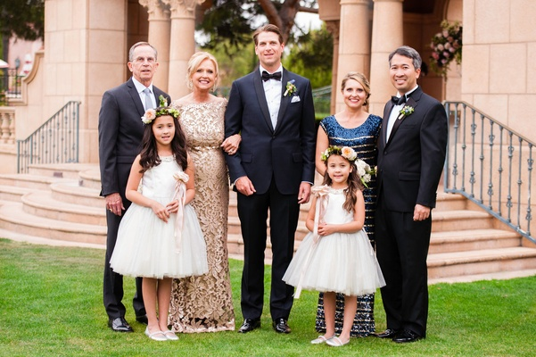 Groom in tuxedo with family champagne dress and flower girls in short white dresses wands