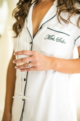 bride in summer pajamas with mrs. sahn embroidered on pocket champagne glass engagement ring