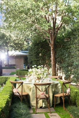 napa woodlands inspired tablescape greenery in a garden wooden chairs green table linens outdoors