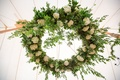 Wedding reception rustic tent reception with greenery wreath white flowers rafters