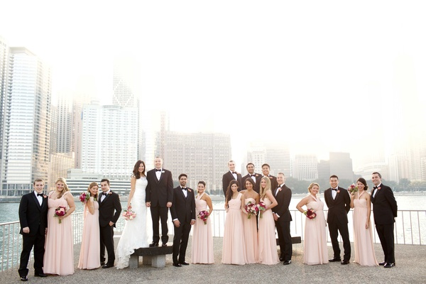 Bridesmaids in long blush dresses with burgundy bouquets groomsmen bride groom in Chicago skyline