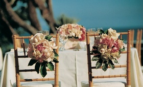Table with floral centerpiece and flowers on chair