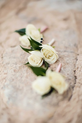 Three groomsmen boutonnieres with two white rose flowers each and pink ribbon