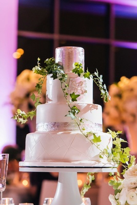Four layer white wedding cake with silver leaf details, monogram, green vine ivy decor